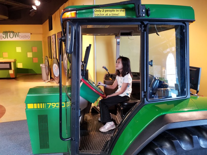 9-year-old girl sitting in a green tractor at the Saskatchewan Science Centre