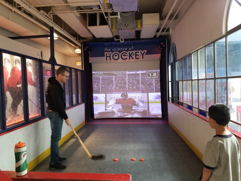 Man getting ready to shoot pucks at the hockey video game screen at the Saskatchwean Science Centre