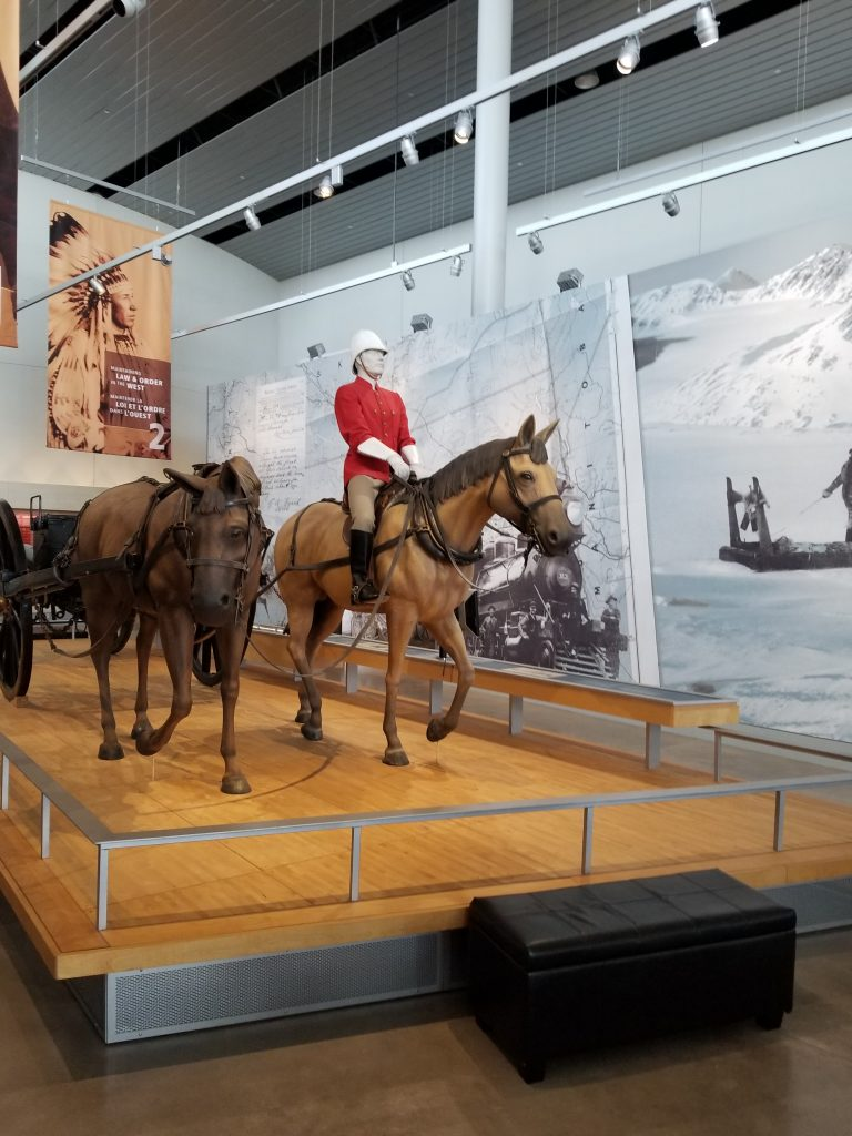 "RCMP Heritage Centre display showing statues of horses with a ""mountie"" atop one."