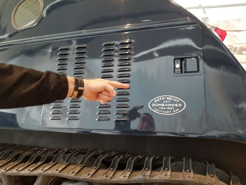 """Mans hand pointing to """"Bombardier"""" on the side of a snow vehicle at the RCMP Heritage Centre in Regina, Saskatchewan"""