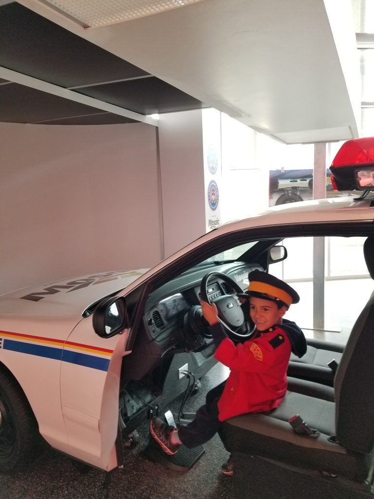 Boy sitting in driver's seat of display RCMP car at RCMP Heritage Centre, Regina, Saskatchewan
