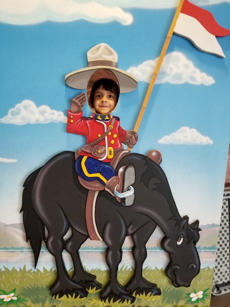 4-year-old girl with her face in a cutout poster of a cartoon mountie on a horse, RCMP Heritage Centre, Regina, Saskatchewan
