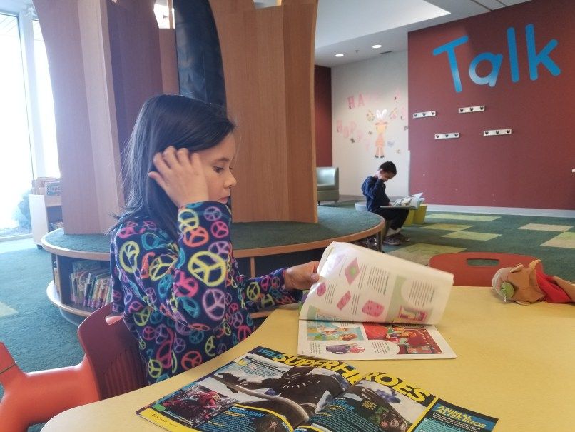 9-year-old girl reading a magazine at a table at Charleswood Public Library in Winnipeg, Manitoba. 6-year-old boy is sitting on a stool in the background, reading a book.