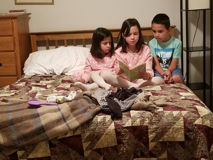 a 9-year-old girl reading a book to her younger siblings. The 4-year-old sister is to her left, and the 6-year-old brother is to her right. They are sitting on a bed.