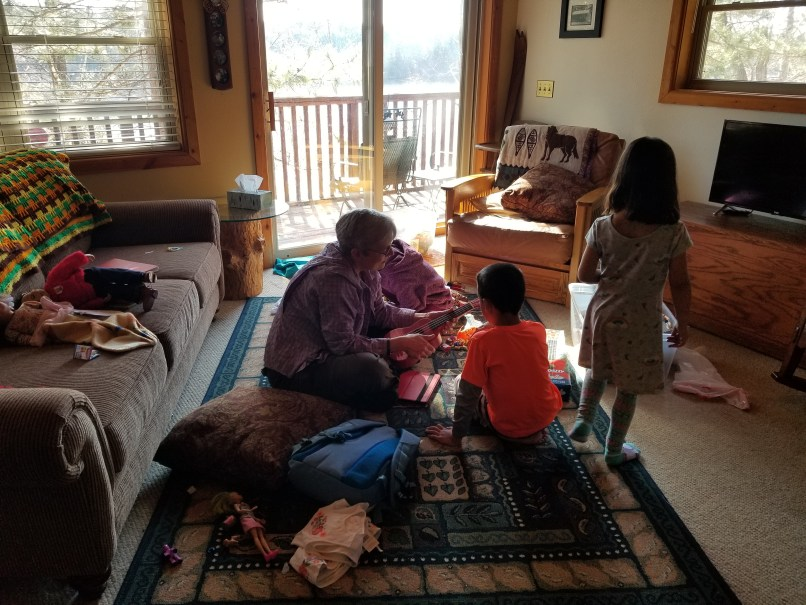 A woman sitting o the floor, playing with three children.