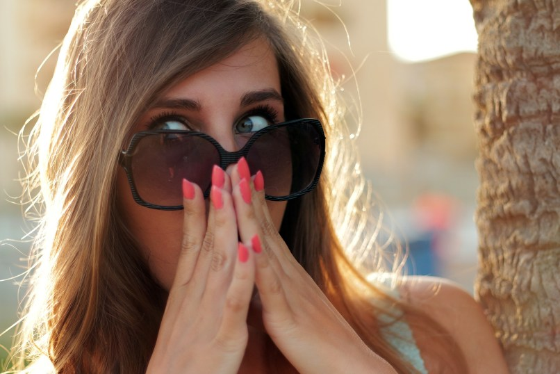 woman wearning large sunglasses, holding hands up to her face and looking shocked