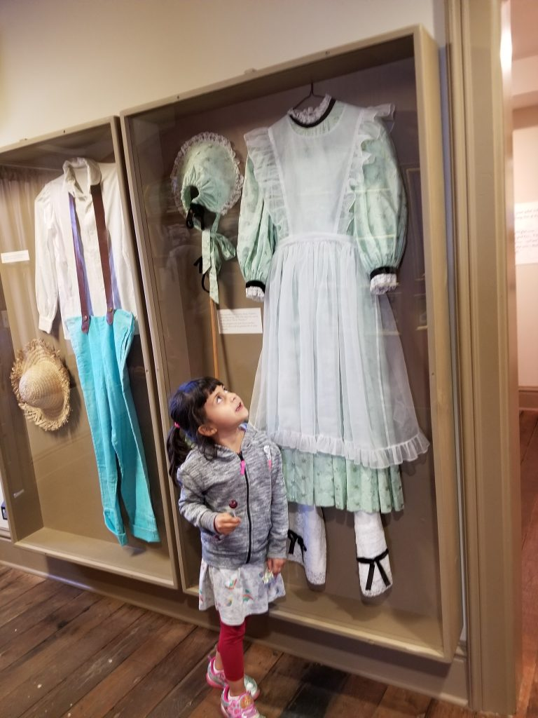 Girl looking up at a display case showing a dress.