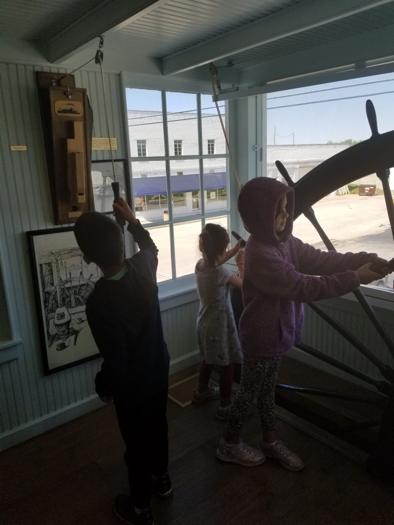 Children at a ship's wheel at the Mark Twain Museum