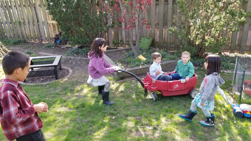 girl pulling two boys in a wagon while a girl and a boy look on