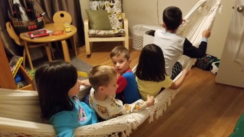 Five children sitting in a hammock