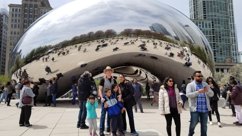 """Father, mother, two daughters and a son standing in front of """"Cloudgate,"""" also known as """"the bean,"""" Millennium Park, Chicago"""