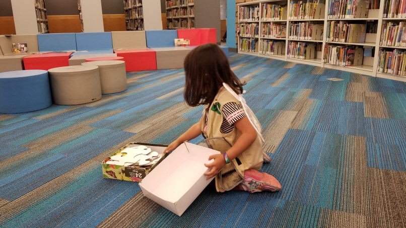 Girl wearing an explorer vest and fairy wings while picking up a puzzle at the Harold Washington Public Library
