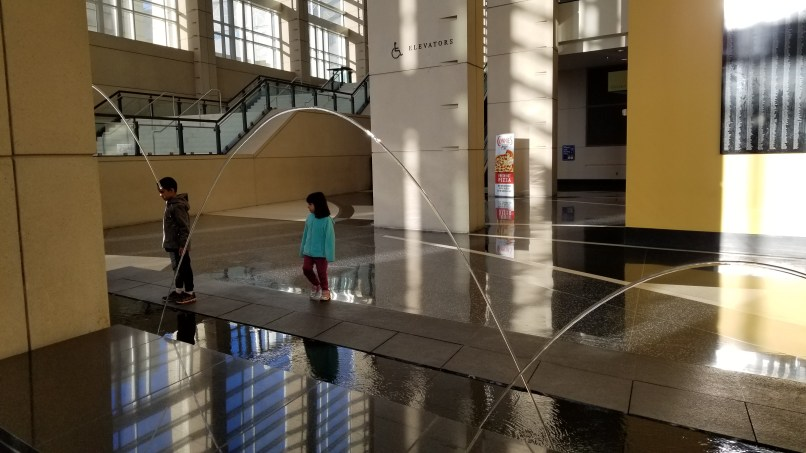 Two children looking at the water arcs at McCormick Place in Chicago.