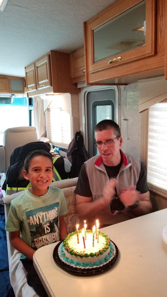 A father sitting next to his son in front of a birthday cake with lit candles on it.
