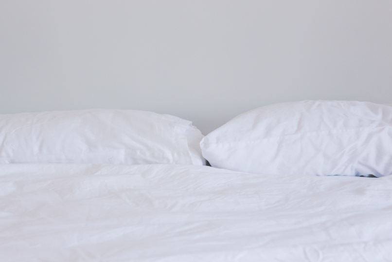 bed with while pillows and sheets. Photo by Nicole Honeywill on Unsplash