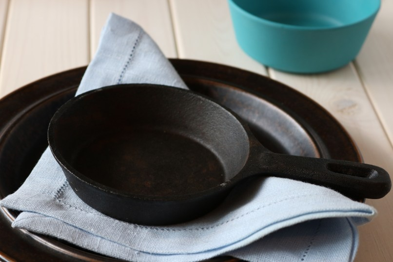 cast iron frying pan on top of a napkin and metal dish. A blue bowl is in the background. Photo by stina_magnus on PIxabay