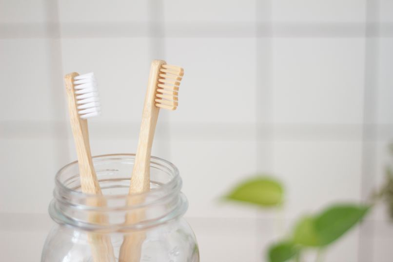 2 bamboo toothbrushes in a glass jar. Photo by Superkitina on Unsplash
