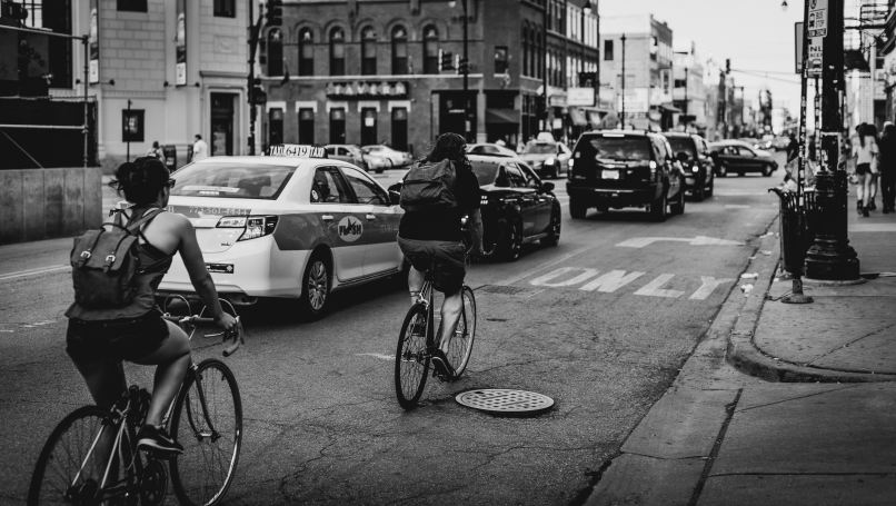 people cycling beside cars