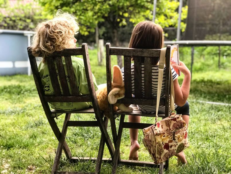Kids' books we read this week. Photo of two girls sitting on wooden chairs outside, reading books. Photo by Max Goncharov on Unsplash.