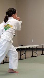 9-year-old girl in martial arts uniform setting up for a kick