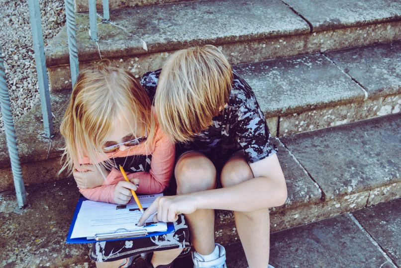 The Ultimate List of Free Homeschooling Resources on www.marianamcdougall.com. Photo description:Boy and girl sitting on a step and leaning over a clipboard. The girl is wearing sunglasses. Photo by Rachel on Unsplash
