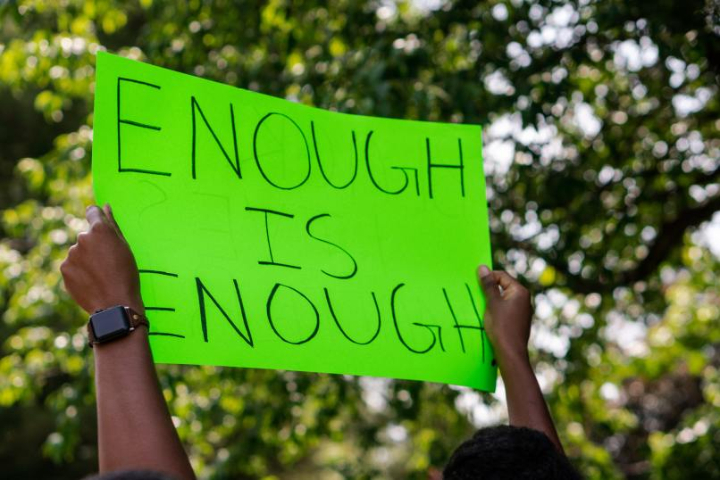 "Black hands holding a neon green sign that says ""Enough is Enough."" Photo by Andrew Robinson on Unsplash."
