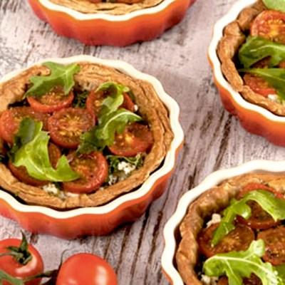 Små terter med fetaost, ruccola og tomat