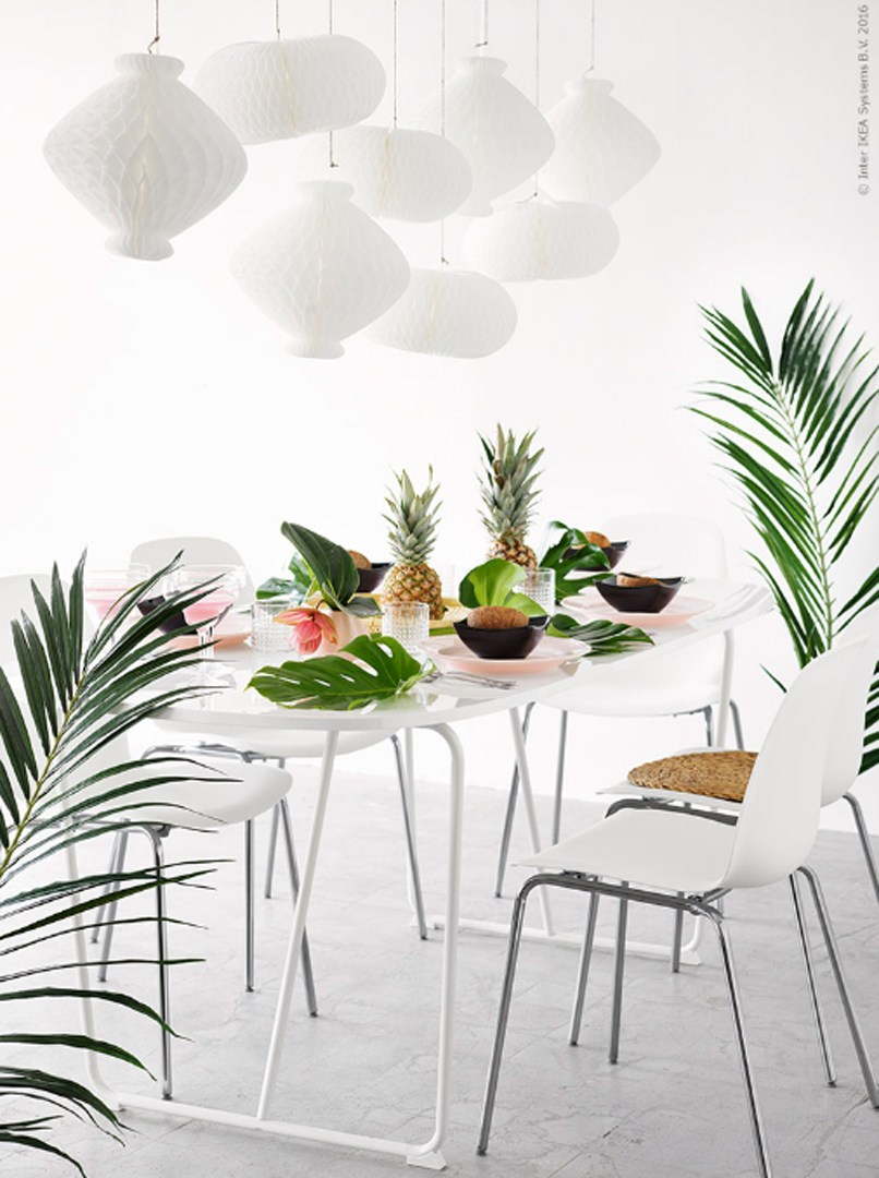 A tropical table setting with palm leaves and pineapple