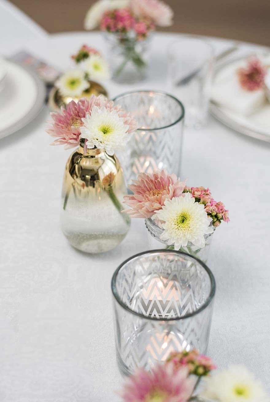 Small vases with flowers on table setting