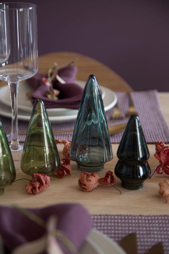 Bord dekket med juletrær i glass i ulike grønne nyanser.