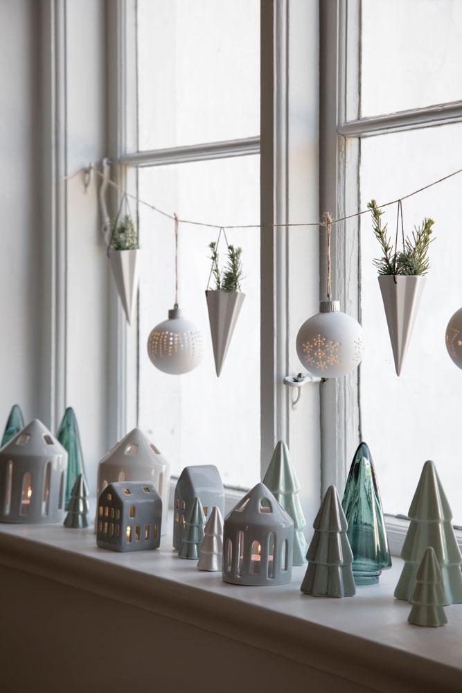 Lyshus og juletrær i keramikk i julevinduet.