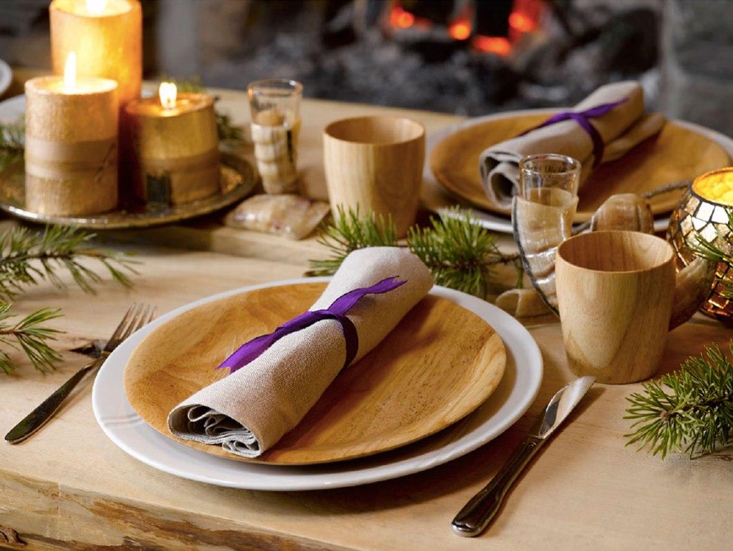 Julebord dekket med tilbehør fra naturen; kvister og grener, kongler og furu.