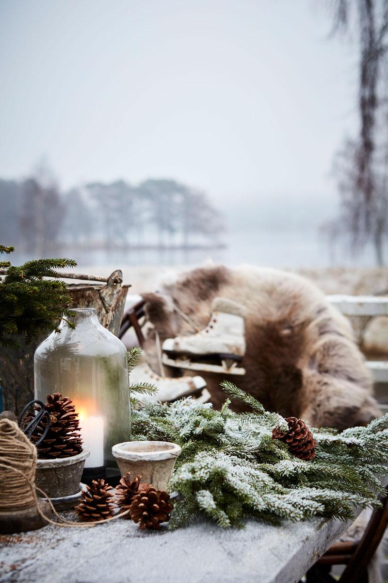 Julepyntet ute med skinn, granbar, furukongler og et par skøyter.