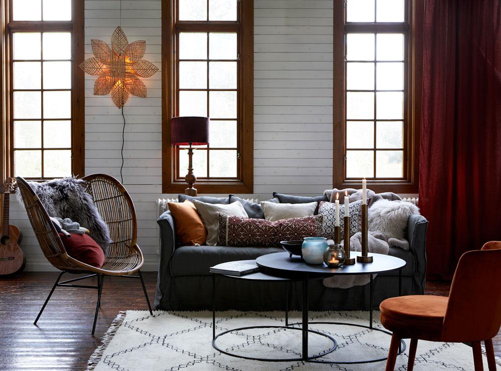 Julestemning i stue med puter og gardiner i rødt.