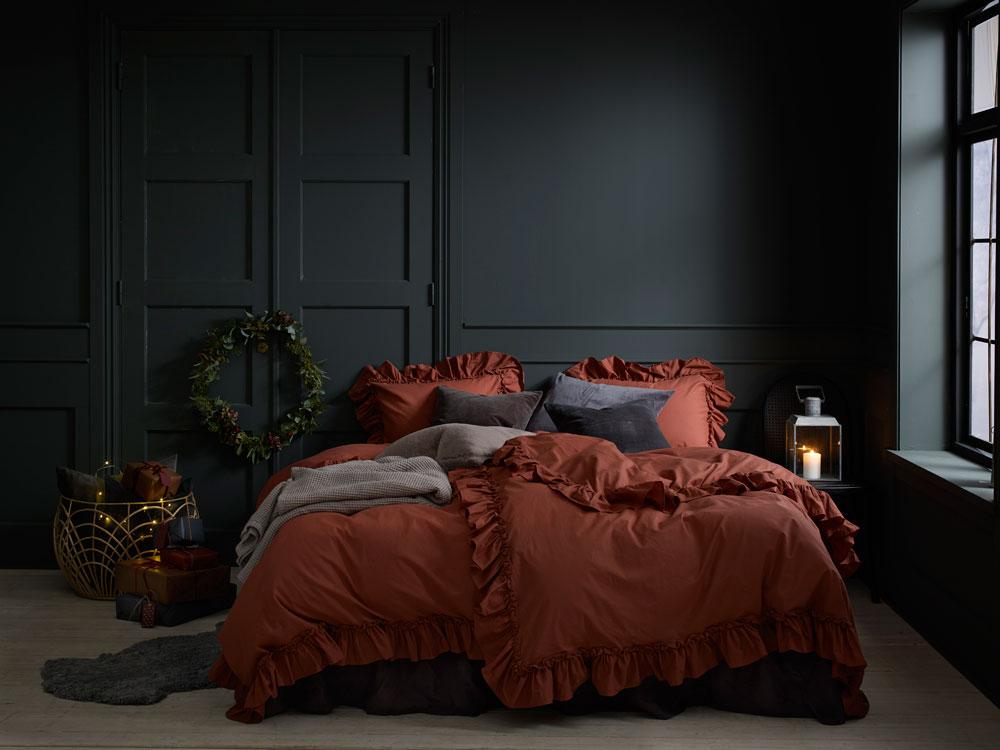 Soverom i mørke farger julepyntet med stor krans.