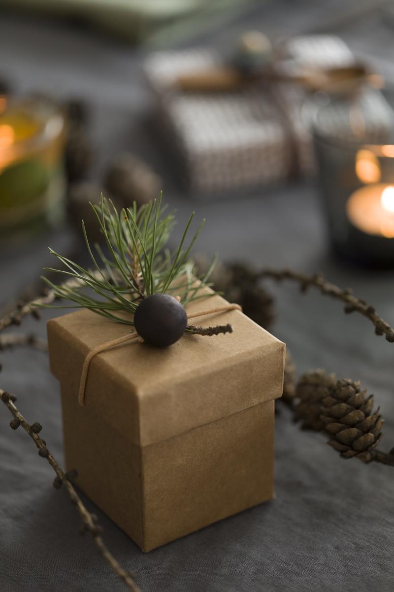 Julegaven er en eske med skinnsnor rundt lokket og treperle til pynt.
