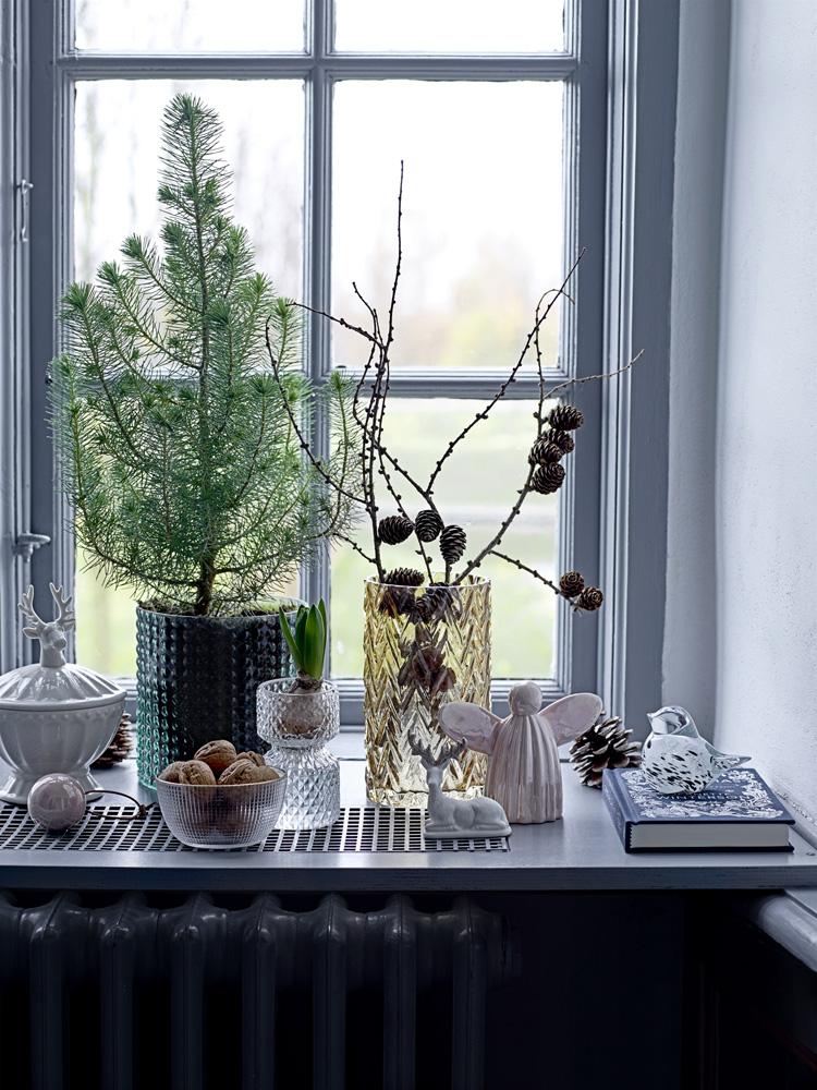 Julepyntet vinduskarm med gran og lerkekvister, svibel, nøtter og julepynt.