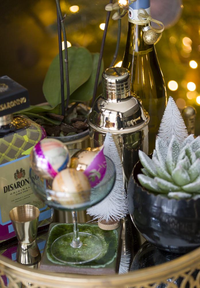 Cocktailglass med juletrekuler på glassbrikke med geode.