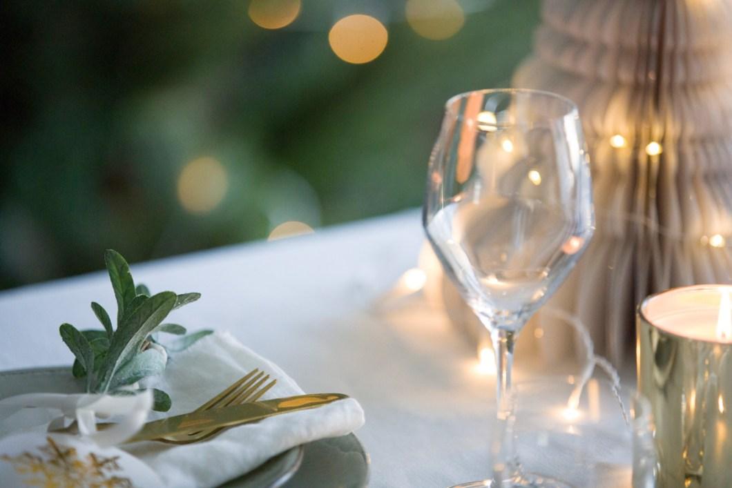 Skap stemning med lyslenker, juletre og fint dekket bord.