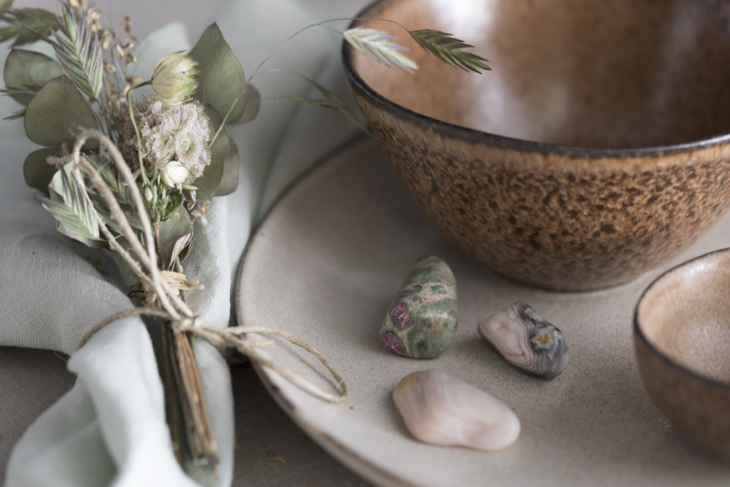 Borddekking med steiner (krystaller), tørkede blomster og strå