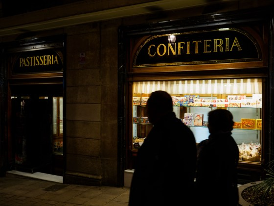 A couple walks in front of classic cakes shop in Carrer Ferran, Barcelona