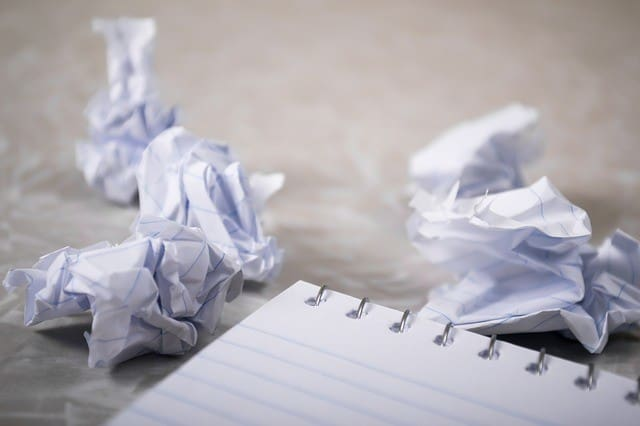 A notepad surrounded by crumpled up pieces of notepaper