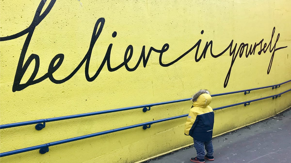"""Image of child standing in front of a wall that has """"Believe in Yourself"""" written on it."""