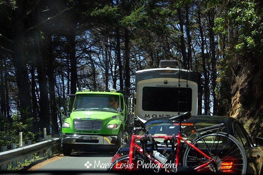 vehicles passing on a a narrow curving stretch of Highway 1. The Pacific Coast Highway
