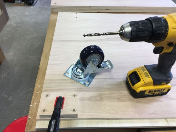 Drilling caster mounting holes in saw stand bottom panels using another shop made jig