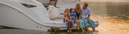 Boating Parts and Accessories  MarineMax family sitting on rear deck of boat dip their feet in warm afternoon waters