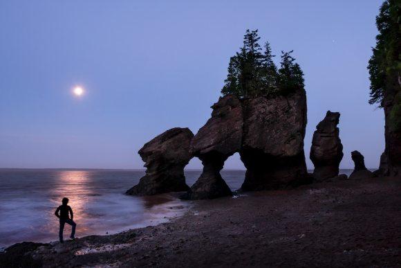 Luna y hombre en Hopewell Rocks en el Parque Nacional de Fundy