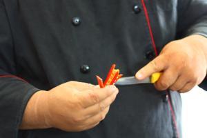 A vietnamese chef slicing chili