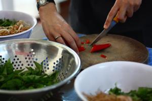 A lady slicing chili