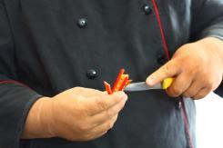 Photo of a Vietnamese chef slicing chili